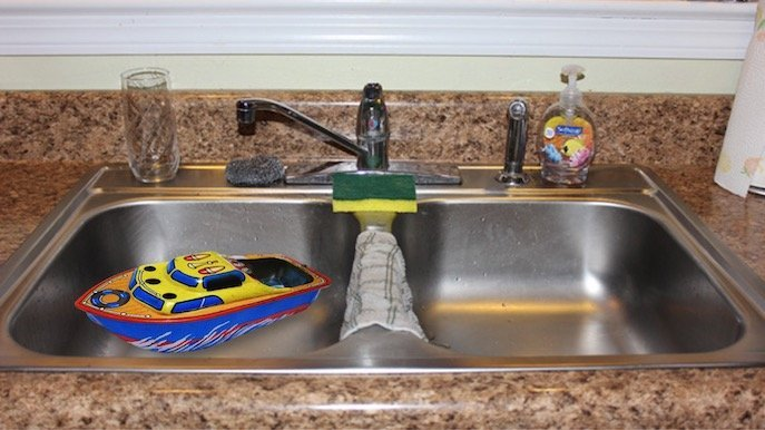 Toy boat in kitchen sink for homeschool science buoyancy experiment